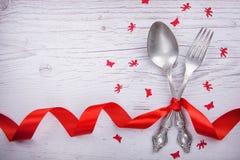 Tappningsked och gaffel med en pappersexercis, änglar och fjärilar för dag för valentin` s på ett trä Arkivbilder