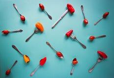 Tappningskedar, gafflar och knivar med paprika och körsbärsröda tomater på blå bakgrund arkivfoton