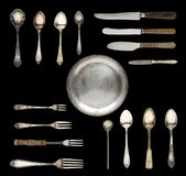 Tappningskedar, knivar, gafflar och en platta som isoleras på en vit bakgrund royaltyfri fotografi
