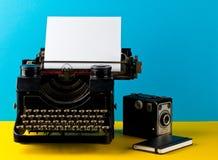 Tappningskrivmaskin med det tomma tomma arket av papper, kamera och Arkivfoto