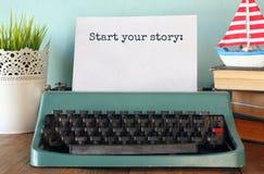 Tappningskrivmaskin med uttryck: STARTA DIN BERÄTTELSE arkivfoto