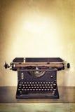 Tappningskrivmaskin på det gamla skrivbordet med Grungebakgrund Royaltyfri Fotografi