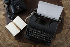 Tappningskrivmaskin, telefon, penna och papper Arkivfoto