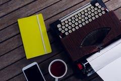Tappningskrivmaskinen, dagboken, svart kaffe och ilar telefonen på trätabellen arkivbilder