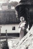 Tappningstående av den unga kvinnan med en tillbringare Royaltyfria Bilder