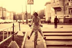 Tappningstående av en flicka med cykeln arkivbild