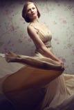 Tappningstående av den lyckliga glamorösa rödhåriga flickan i kall klänning Arkivbild