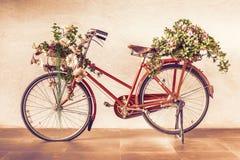 Tappningstil av den röda cykeln med blommakorgar som parkerar mot arkivfoton
