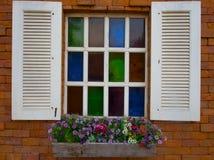 Tappningstilfönster med den färgrika blomman Arkivbild