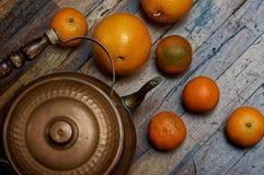 Tappningstilleben i mörka färger Järnkokkärl med apelsiner på skrapade bräden Royaltyfria Bilder