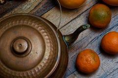 Tappningstilleben i mörka färger Järnkokkärl med apelsiner på skrapade bräden Royaltyfri Foto