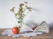 Tappningstilleben med boken, exponeringsglas, äpplet och vasen med blommor på doily Royaltyfri Bild
