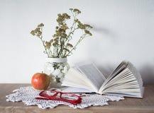 Tappningstilleben med en öppen bok, exponeringsglas, äpplet och vasen med blommor på doily Fotografering för Bildbyråer