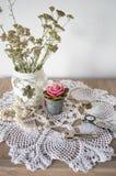 Tappningstilleben med halsbandet, tangenter, klockor, stearinljuset och vasen med blommor på doily Arkivbild
