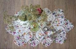 Tappningstilleben med parfume, tangenter, klockor, stearinljuset och vasen med blommor på doily Royaltyfria Bilder