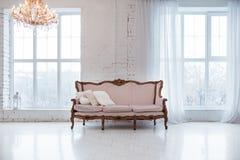 Tappningstilsoffa i inre rum för vind med det stora fönstret royaltyfria foton