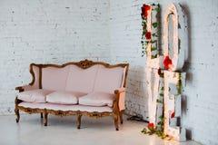 Tappningstilsoffa som dekoreras med blommor i inre rum för vind med det stora fönstret royaltyfria bilder