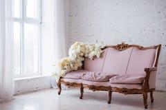 Tappningstilsoffa som dekoreras med blommor i inre rum för vind med det stora fönstret royaltyfri bild