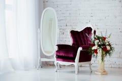 Tappningstilstol i klassiskt inre rum med det stora fönstret och blommor fotografering för bildbyråer
