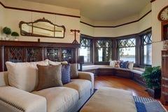 Tappningstilvardagsrum med den beigea soffan och det antika träkabinettet Royaltyfri Bild
