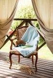 Tappningstol, bok och kaffe i den träträdgårds- terrassen royaltyfri foto
