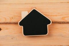 Tappningsvart tavla som hänger på träbakgrund svart tavla med stället för din text Arkivfoto