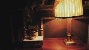 Tappningtelefon och retro skrivbordlampa på tabellen arkivfilmer