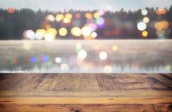 tappningträbrädetabell framme av det abstrakta fotoet av den dimmiga och dimmiga sjön på morgonen/aftonen arkivfoto