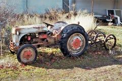 Tappningtraktor och verktyg framme av ladugården arkivbilder