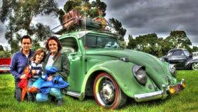 Tappningtysk Volkswagen Beetle och familj Fotografering för Bildbyråer