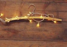 Tappningvärme trähängaren med guld- jul guld- girlandljus på trälantlig bakgrund Filtrerad bild Fotografering för Bildbyråer
