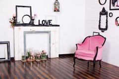 Tappningvelorfåtölj, i ett ljust rum och en konstgjord spis Inre loft med trävita väggar Bildramar på th arkivfoton