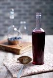 Tappningvinflaska med hemlagad svart vinbär-, blåbär- och björnbärvinäger Arkivbilder