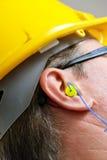 Tappo per le orecchie giallo nella fine dell'orecchio su fotografia stock