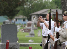 Taps bugler at memorial day service. Color Guard veterans in uniform with guns lined up at cemetery for Memorial Day service with a man playing TAPS on a bugle Royalty Free Stock Images