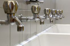 Taps lined up and a white ceramic washbasin. Many taps lined up and a white ceramic washbasin royalty free stock photo