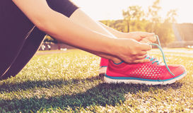 Taqueur femelle attachant des chaussures sur le champ de stade Image stock