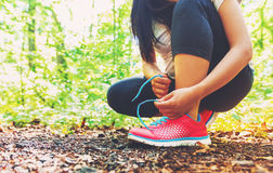 Taqueur femelle attachant ses chaussures dans les bois Images libres de droits
