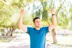 Taqueur masculin avec des bras augmentés célébrant le succès en parc photographie stock