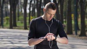 Taqueur masculin fonctionnant et écoutant la musique s'arrêtant aux traqueurs de smartphone et de smartwatch de contrôle banque de vidéos