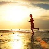 Taqueuse de jeune femme au coucher du soleil sur le bord de la mer Images libres de droits