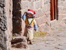 TAQUILE海岛,普诺,秘鲁 2013年5月31日:传统上使用在他的房子前面的加工好的小孩 免版税库存图片