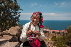 TAQUILE海岛,普诺,秘鲁- 2016年10月13日:关闭老秘鲁人编织的帽子画象用在湖T的传统方式 免版税库存照片