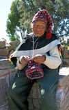 Man on Taquile Island, Lake Titicaca, Peru. TAQUILE ISLAND, LAKE TITICACA, PERU - June 25, 2019 - A elderly native man of Taquile Island knits a traditional hat stock photography