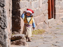 TAQUILE ISLAND, PUNO, PERU. MAY 31, 2013: Traditionally dressed toddler playing in front of his house Royalty Free Stock Image