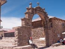 Taquile island in Puno, Peru. PUNO, PERU - NOVEMBER 14, 2016: A local man rests in the gate of Taquile island in Puno, Peru Stock Photography