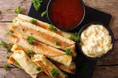Taquitos med höna- och ostnärbild såväl som såser Ho Arkivfoto