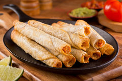 Taquitos. A platter of delicious chicken taquitos with salsa, guacamole, and lime Royalty Free Stock Image