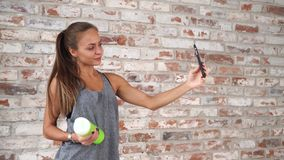 Tar den iklädda sportswearen för flickan selfie vid telefonen nära tegelstenväggen i en idrottshall arkivfilmer