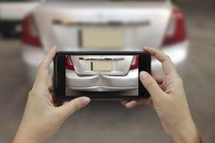 Tar den smarta telefonen för handinnehavet ett foto på platsen av cras för en bil Royaltyfri Bild